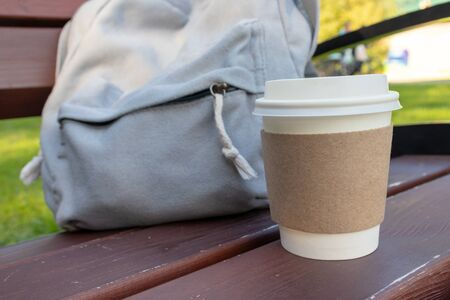 A craft disposable paper cup of coffee and a backpack on a bench in park, coffee brake on the open air. 写真素材