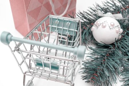 Empty shopping cart, trolley on white background with craft paper shopping bag and green decorated fir tree branches.
