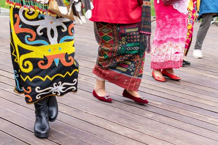 Moscow, Russia - August 02, 2019: Indonesian women wearing traditional clothes dancing together during national asian festival. Reklamní fotografie - 137615844