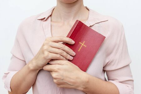 Young praying christian womans hands holding holy bible with a cross on a cover.