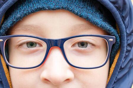 eyes of an intelligent teenage boy wearing blue fashionable stylish glasses close up, outdoors. Reklamní fotografie - 137123538