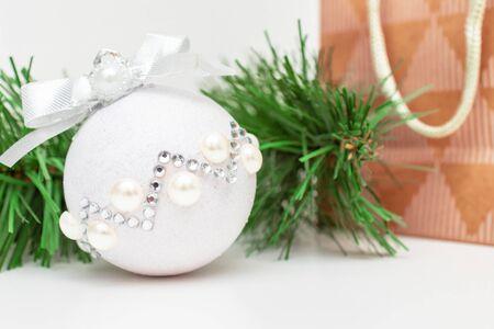Christmas shopping - a branch of fir pine tree, shiny decorative christmas ball and acrast paper bag e on white background. Reklamní fotografie - 137125034