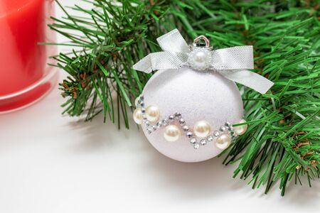 Christmas mood - a branch of fir pine tree, shiny decorative christmas ball and a red candle on white background with copy space.