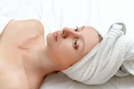Spa skin care beauty woman wearing wrapped hair towel on a head after beauty treatment, Caucasian woman lying on white sheet. Reklamní fotografie - 137125265
