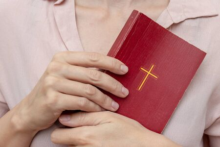 Young praying christian woman's hands holding holy bible with a cross on a cover. Reklamní fotografie - 137126433