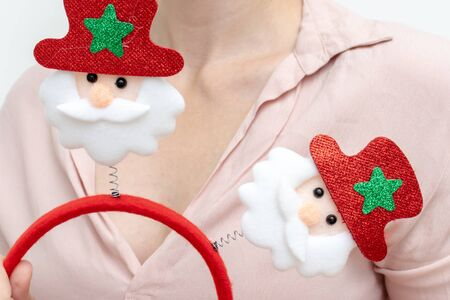 Woman holding christmas carnival costume accsessory rim with santa clauses close up. Reklamní fotografie - 137126436