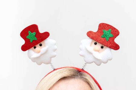 Christmas decorative santa claus accessories on the head of blond woman on white background. Reklamní fotografie - 137126500