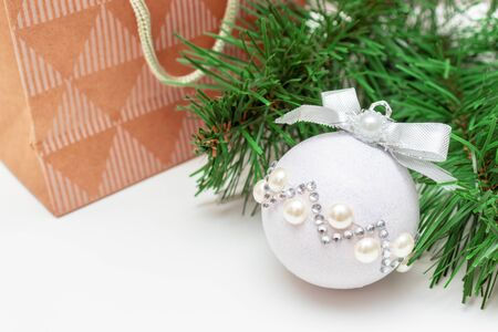 Christmas shopping - a branch of fir pine tree, shiny decorative christmas ball and acrast paper bag e on white background with copy space. Reklamní fotografie - 137126501