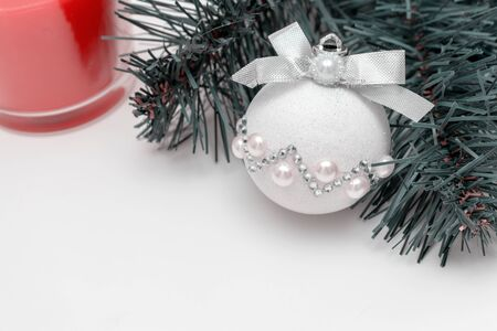 Christmas mood - a branch of fir pine tree, shiny decorative christmas ball and a red candle on white background with copy space. Reklamní fotografie - 137126502