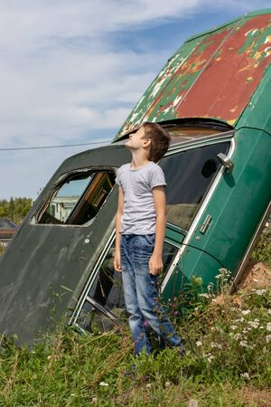 Thoughtful caucasian teenage standing on the grass in countyside in summer day with serious face expression, a retro car is on background. Reklamní fotografie - 137126569
