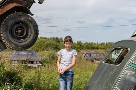 Thoughtful caucasian teenage standing on the grass in countyside in summer day with serious face expression, a retro car is on background. Reklamní fotografie - 137126699