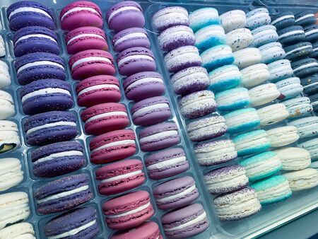 A lot of macarones, macaroons in blue color lying in a row in a candy store. Reklamní fotografie - 137126715