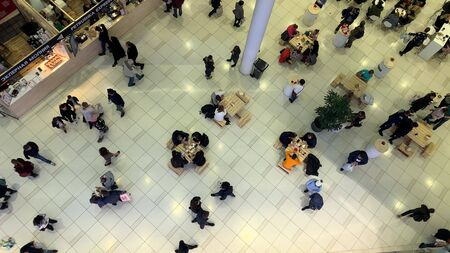 Moscow, Russia - November 13, 2019: A lot of people walking and sitting by the tables, eating in a cafe at foodcourt in shopping mall, center Redakční