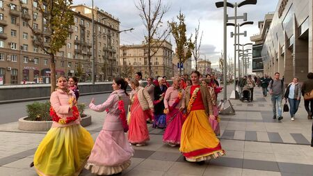 Moscow, Russia - November 12, 2019: Hari Krishna people, women in colorful sari walk along the street, sing and dance, holiday parade of Krishnas
