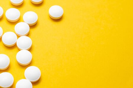 Many white tablets close up on yellow background with copy space, autumn and winter viral disease , infection. Reklamní fotografie