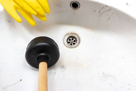Blocked sewer, clogged wash bowl, basin drain, yellow rubber gloves and a plunger near in the bathroom at home.