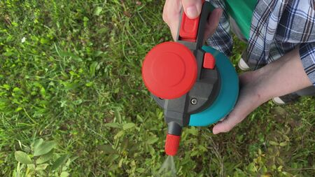 Woman gardener spraying fruit trees and bushes against plant diseases and pests using spray bottle withinsecticide solution in the garden, close up. Reklamní fotografie - 137158145