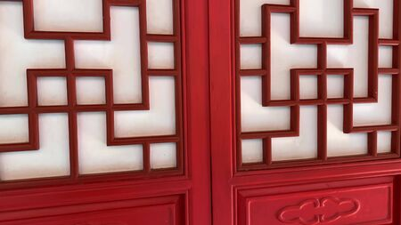 Red wooden carved decorative doors in chinese style, asian traditional ornament for decorating home, walls and doors. Reklamní fotografie - 137158150