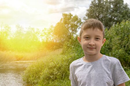 Portrait of happy smiling preteen boy outdoors in summertime, green nature and sunlight on background