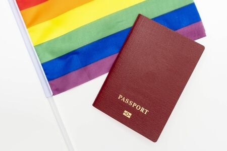 lgbt rights and searching for asylum and migration concept, and rainbow gay pride flag and red passport on white background