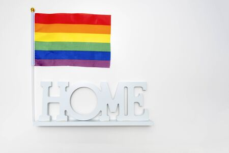 Lgbt rainbow gay pride flag and a sign home on white background. Archivio Fotografico