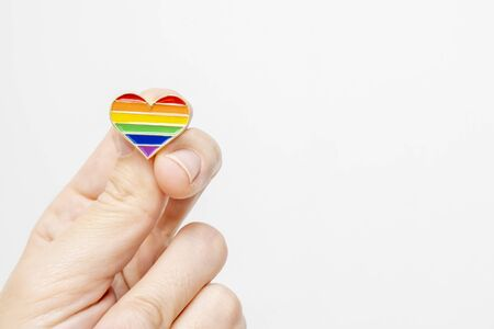 Hand holding rainbow gay pride symbol heart as lgbt rights concept, copy space.