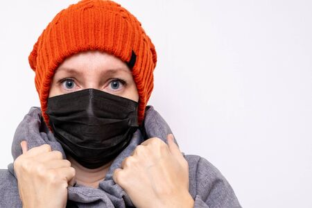 Concept of coronavirus quarantine. Woman in winter clothes and a black respiratory medical surgical mask as a protection from viruses and bacteria.