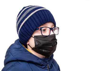Concept of coronavirus quarantine. A boy in winter clothes and a black respiratory medical surgical mask as a protection from viruses and bacteria. Imagens