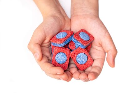 Hands holding many red and blue dishwasher soap tablets close up, white background.