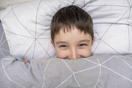 Smiling preteen boy child lying in bed and covering his tricky playful face with a blanket, pranking kid concept