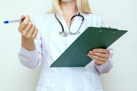 Woman female doctor writing on clipboard a diagnosis and prescription after examination of a patient.