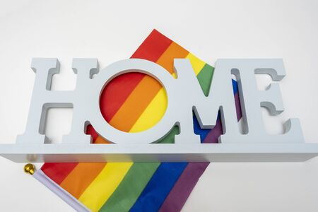 Lgbt rainbow gay pride flag and a sign home on white background