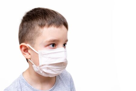 A caucasian boy in white face surgical mask on white background with copy space Reklamní fotografie