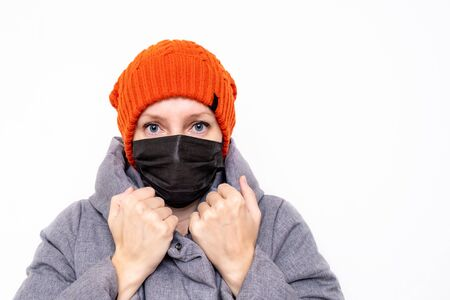 A caucasian woman in winter clothes wearing black face surgical mask as a protection against an epidemic of viral diseases
