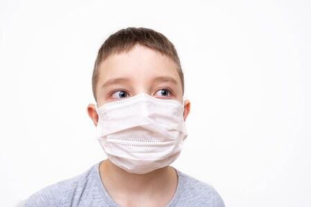 A caucasian boy in white face surgical mask on white background, protection against flu and virus infection