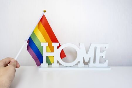 A hand holding lgbt rainbow gay pride flag and a sign home on white background Reklamní fotografie