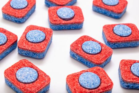 Many red and blue dishwasher soap tablets on white background, kitchen equipment and solutions for washing dishes.