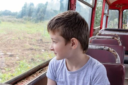 A 10 years boy riding in a old vintage bus, he is sad because his poor life and the bus moving going on a dirty country road.
