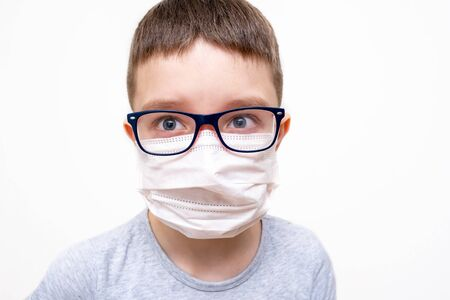 A caucasian boy wearing glasses in white face surgical mask on white background, protection against flu and virus infection.