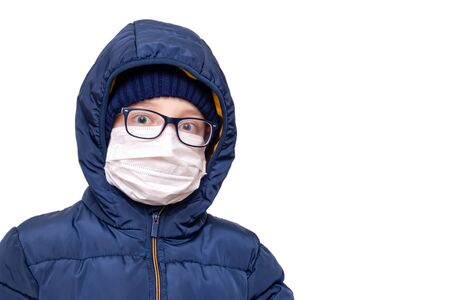 Concept of coronavirus quarantine. A boy in winter clothes and a white respiratory medical surgical mask as a protection from viruses and bacteria.