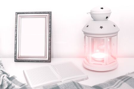 Winter still life interior details, lantern with burning candle, open book and a photo frame on the table. Reklamní fotografie - 140558032