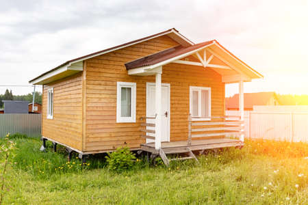 Small tiny wooden frame house with sundeck and white windows and door as a country residence in sunny summer day. Standard-Bild