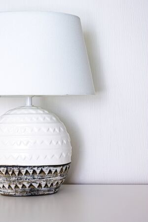 Bedside lamp with ceramic base and textile lampshade on the table. Reklamní fotografie