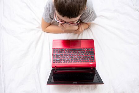 A preteen boy lying on a bed, surfing internet and typing into his blog, child blogging concept. Reklamní fotografie - 141531601