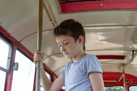A 10 years boy riding in a old vintage bus, he is sad because his poor life and the bus moving going on a dirty country road. Reklamní fotografie - 141531602