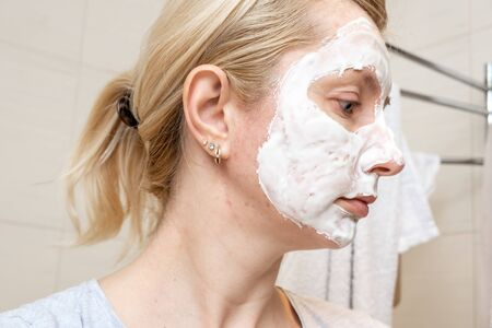 A portrait of a sad woman with problem acne skin making a cleansing purifying white facial mask, anti black spot and acne treatment