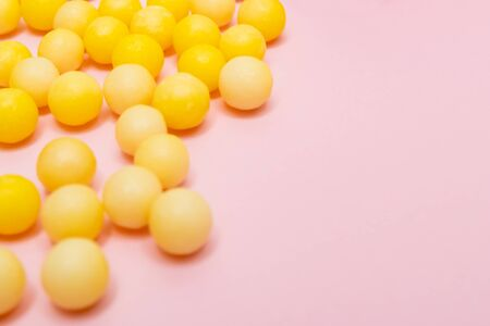 Yellow round dragees of vitamin c, ascorbic acid near a white plastic bottle, container on pink background. Reklamní fotografie