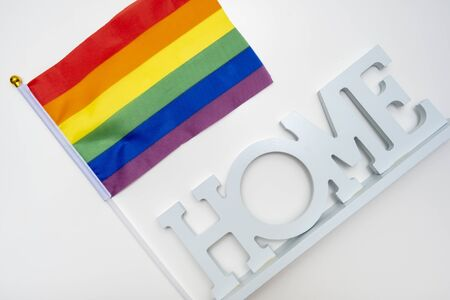 Lgbt rainbow gay pride flag and a sign home on white background. Reklamní fotografie - 140558158