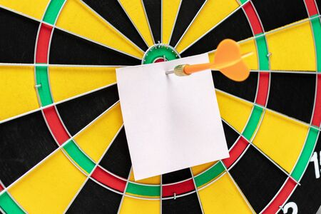 Paper note with copy space on a dart board close up, business target or goal success, online marketing concept. Reklamní fotografie