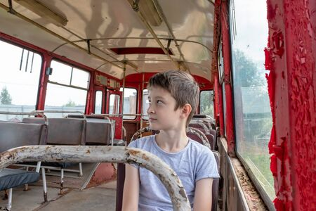 A 10 years boy riding in a old vintage bus, he is sad because his poor life and the bus moving going on a dirty country road. Reklamní fotografie - 141531664